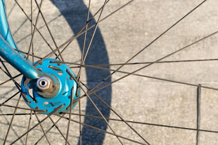 Close-up of blue bicycle front wheel hub and spokes