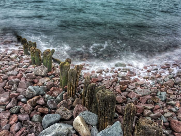 Subdivided Water Sea Pebble Rock - Object Beach Shore Stone - Object Wave Rock Coastline Nature Wooden Post Stone Day Outdoors Rocky Non-urban Scene Water's Edge Large Group Of Objects Coastal Feature