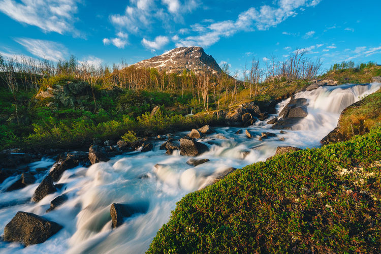 Beautiful view of stream flowing through rocks on land