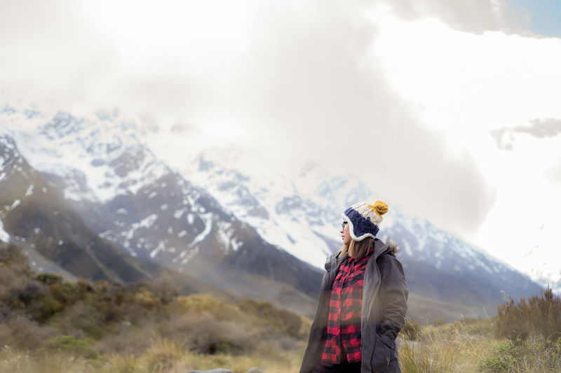 Woman Wearing Warm Clothing While Standing Against Snowcapped Mountain