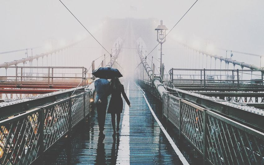 Rear view of couple walking on brooklyn bridge during rainy season