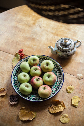 High angle view of apples in plate with dry leaves on wooden table