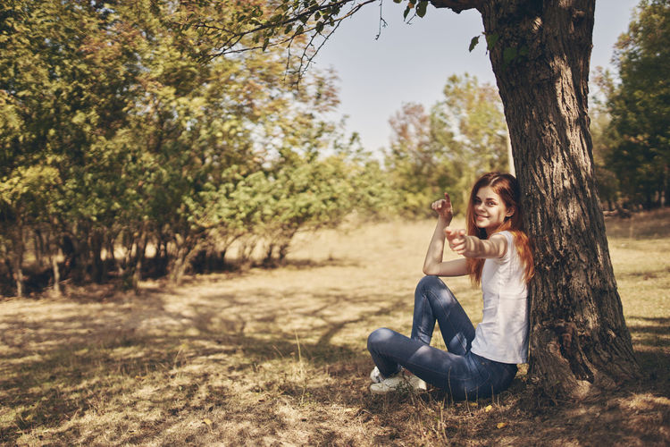 Young couple sitting on tree trunk