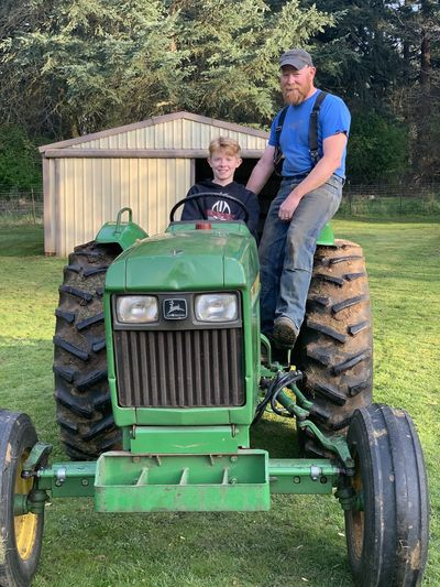 Full length of young man with tractor in grass