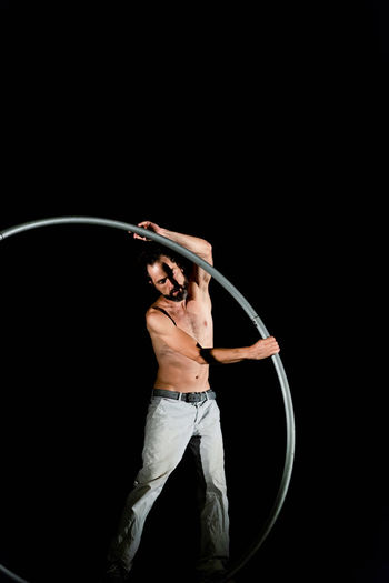 Circus Adult Black Background Expertise Front View Holding Indoors  Men Mid Adult Motion One Person Performance Plastic Hoop Skill  Sport Standing Studio Shot Three Quarter Length Young Adult