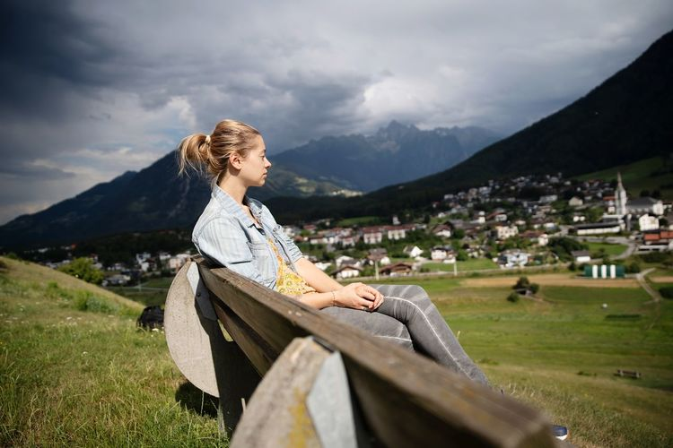 Woman looking away while sitting on bench against cloudy sky