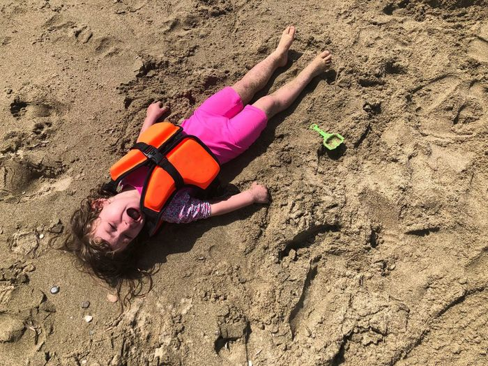 Portrait of boy in life jacket crying while lying at beach