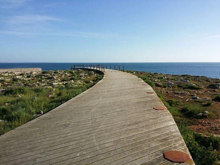 Boardwalk Leading Towards Sea Against Blue Sky