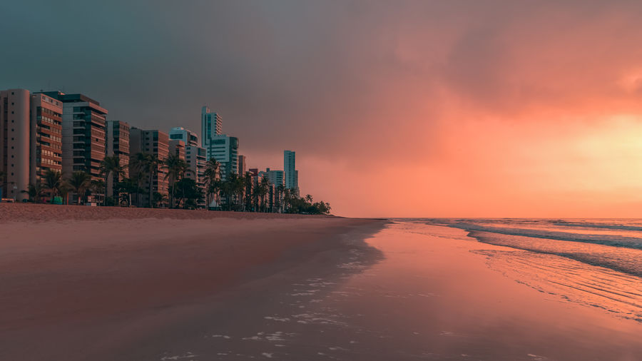 Scenic view of beach with building against sky during sunset