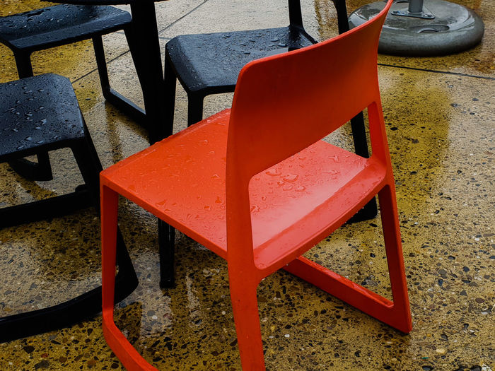 Red among black Exception Step Out Of Line Wet Rainy Damp Water Rain Sitting Outside Outdoors Piece Of Furniture Two-coloured Marketing Advertising Advertisement Close Up Close-up Zoom In Front Black Seat Copy Space Four Chair Red Furniture Urban Scene Arrangement Order Display