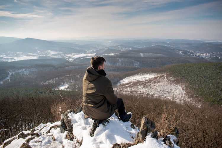Rear view of man sitting on mountain during winter