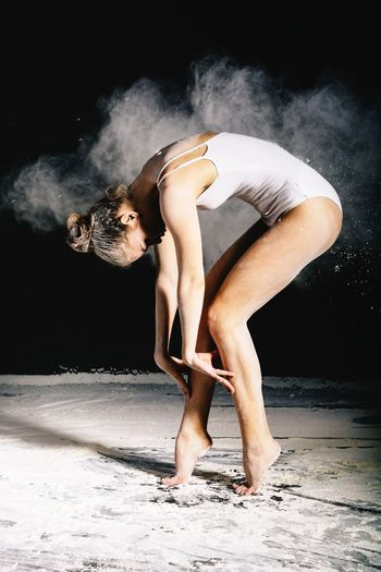 Young woman dancing with chalk powder against black background