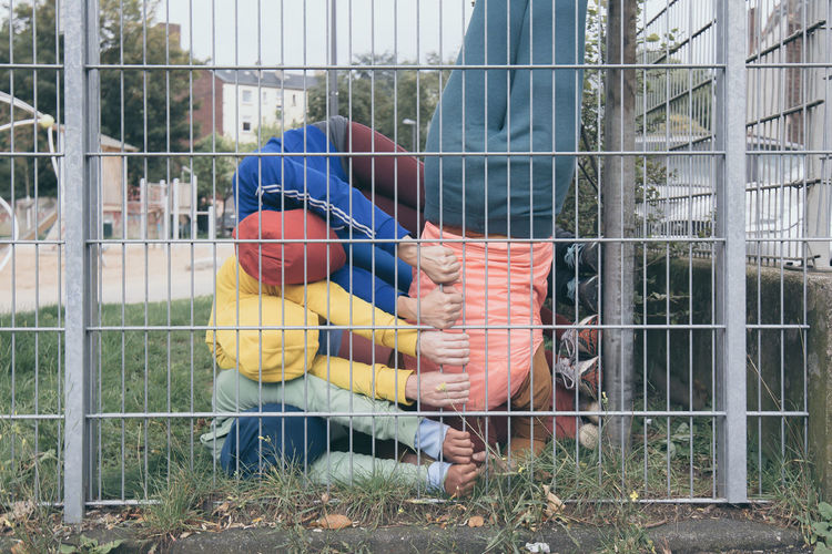 Shot of four children exercising by fences