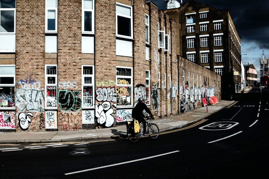 Postcode Postcards Architecture Building Exterior Built Structure Bicycle London City Graffiti Transportation Real People City Life Biker Outdoors Motorcycle Men One Person Day Full Length Only Men Sky One Man Only Adult