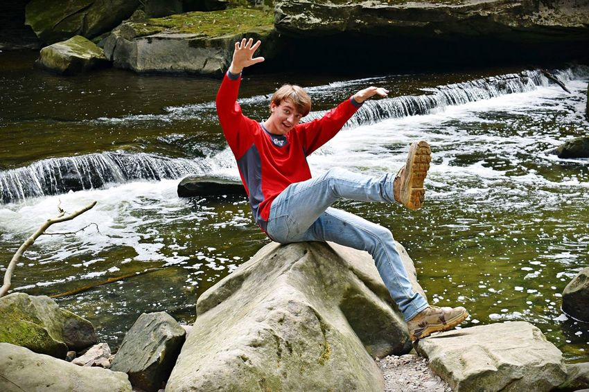 Falling Full Length Rock Leisure Activity Water Real People Solid One Person Sitting Front View Human Arm River Outdoors High Angle View Nature Casual Clothing Rock - Object Lifestyles Sunlight Day Arms Raised