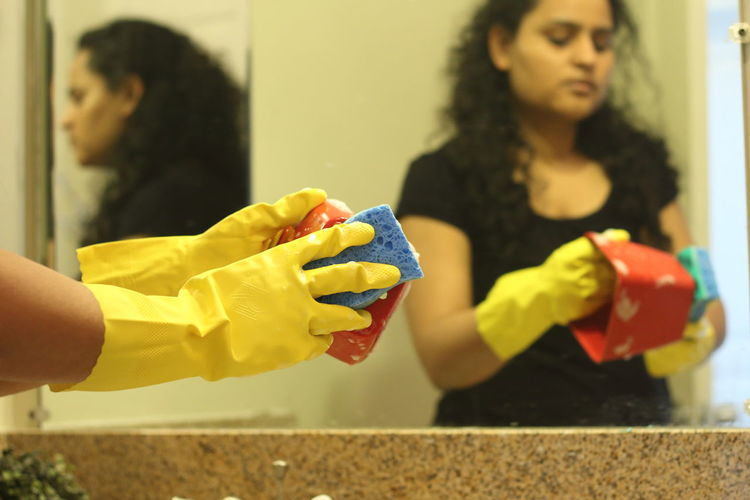 Cropped Hands Of Mid Adult Woman Cleaning Container At Home