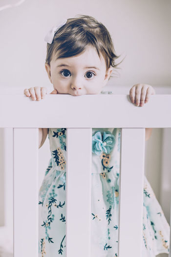 Portrait of cute baby girl standing in crib at home