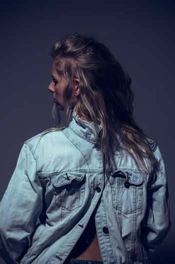 Rear view of woman wearing denim jacket standing against gray background