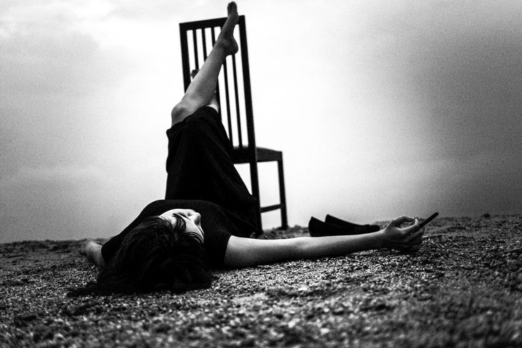 Woman lying on shore by chair against sky