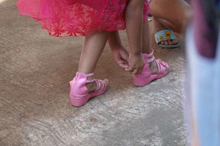 Low section of women wearing pink shoes