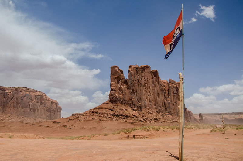Low angle view of flag on desert against sky