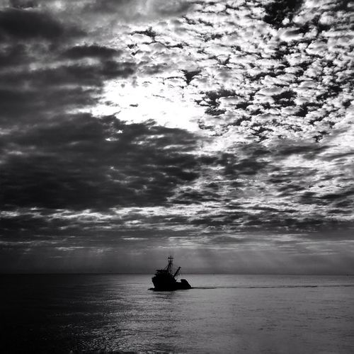 Silhouette boat sailing on sea against sky