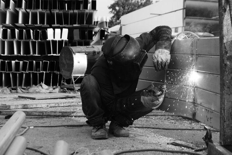 Worker welding metal in workshop