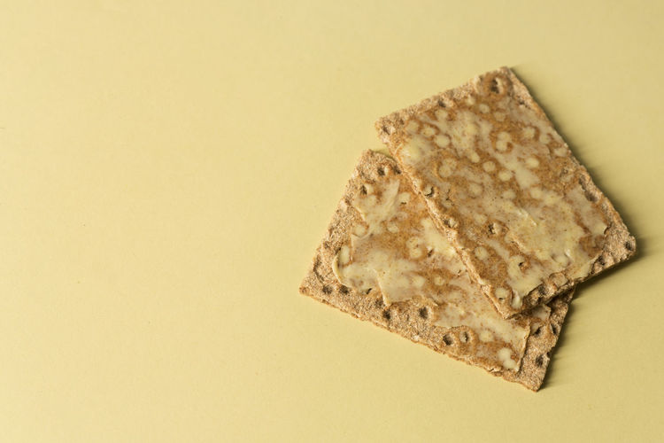 Close-up of buttered rye crackers with butter - on pastel yellow background - minimal- copy space EyeEmNewHere Yellow Studio Shot Still Life Simple Food Simple Rye Crackers Rye - Grain Pastel Yellow Pastel Colors Minimalism Minimal High Angle View Food Crackers Close-up Butter Biscuits After School Snack Ready To Eat Fun From Above  Diet Copy Space Bright Colors