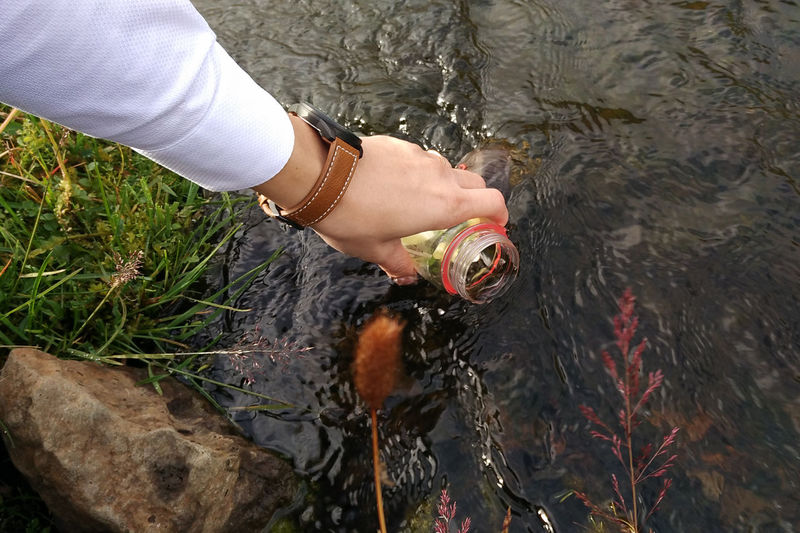 Hiker taking water in river using tumbler Bottle Clear Sky Drinking Freshness Hanging Out Mineral Nature Outdoors River Riverbank Trekking Water Young Adult