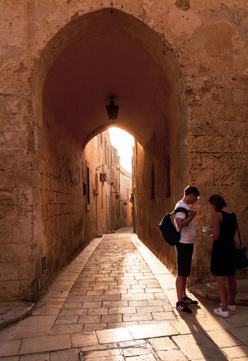Malta Mdina Architecture Adult Arch Architecture Building Built Structure Casual Clothing Day Direction Full Length History Leisure Activity Lifestyles Maltaphotography Mdina Men Outdoors People Real People Rear View Standing Two People Walking Women