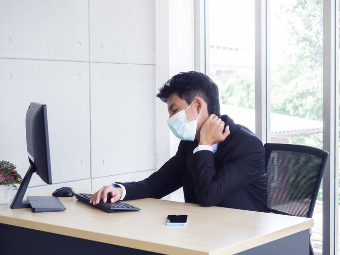 Young businessman wearing flu mask working at office