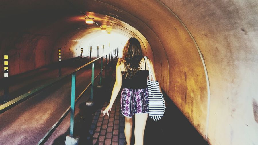 Rear View Of Woman Walking In Tunnel
