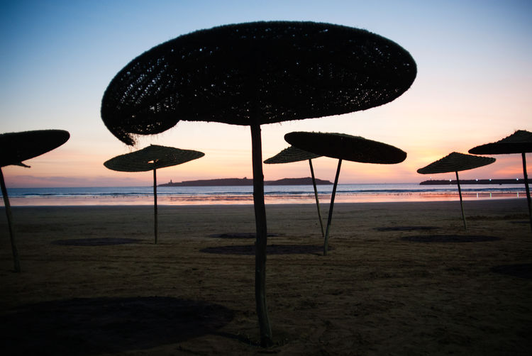 Silhouette parasols on beach against sky during sunset