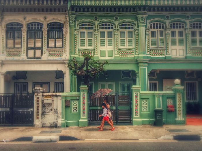 A woman and a child walk past the row of pre-war peranakan houses along Koon Seng Road in Singapore on a hazy day Streetphotography