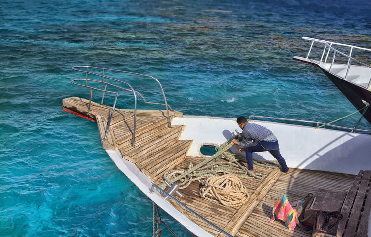 EyeEmNewHere Egypt Adult Boat Boat Worker Day Fisherman Full Length High Angle View Men Mid Adult Mode Of Transportation Nature Nautical Vessel Occupation One Person Outdoors Railing Real People Red Sea Red Sea Hurghada, Egypt Sea Three Quarter Length Transportation Tying Rope Tying Ropes Water