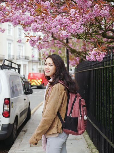 Woman standing by pink flowers on sidewalk in city