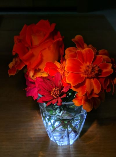 High angle view of red roses in vase on table