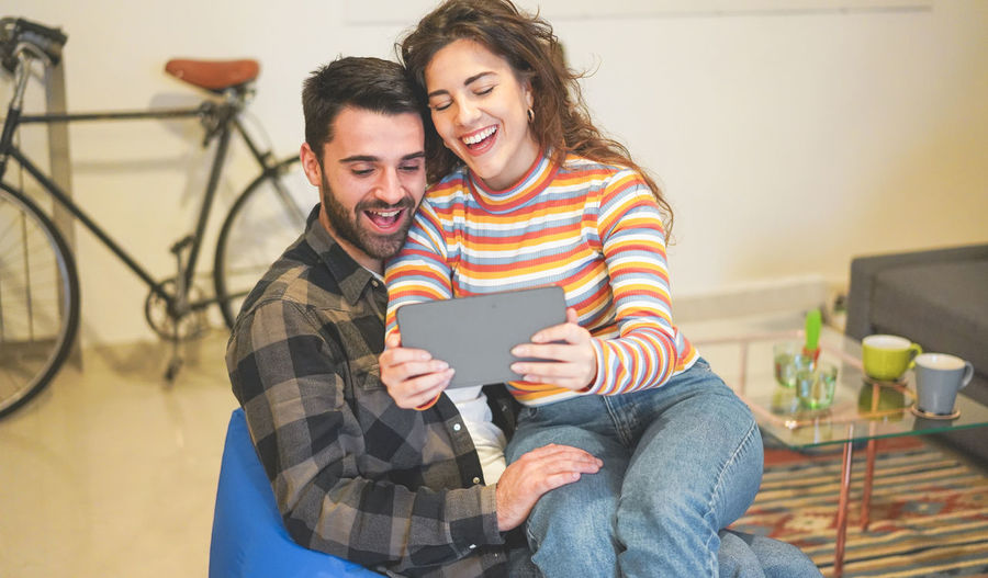 Cheerful woman taking selfie with boyfriend while sitting at home