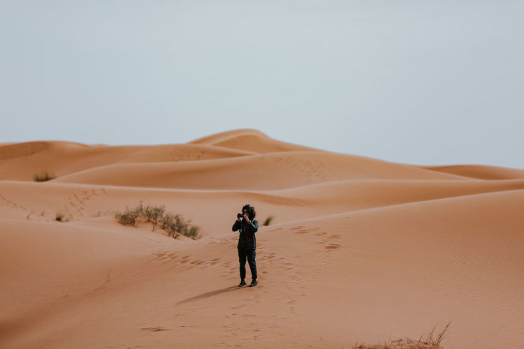 Full length of man photographing while standing on sand in desert against sky