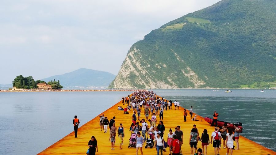 People On Pier Over River Against Mountain