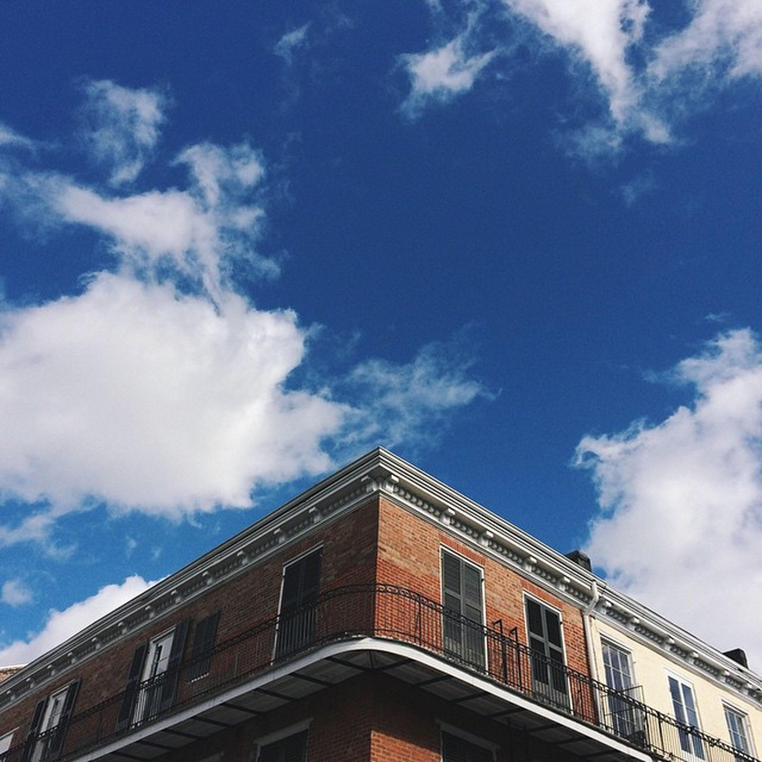 architecture, built structure, low angle view, building exterior, sky, blue, cloud - sky, cloud, building, high section, window, residential building, residential structure, day, outdoors, city, house, no people, railing, cloudy