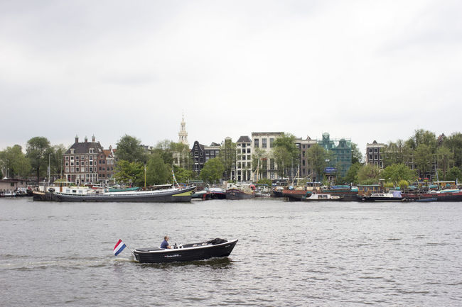 Amsterdam Cloudy Dutch Flag Netherlands Architecture Boat Boats Building Exterior Buildings And Sky Built Structure Canal Canals And Waterways City Cityscape Day Dutch Holland Nature Nautical Vessel One Person Outdoors River Transportation Travel Destinations Water