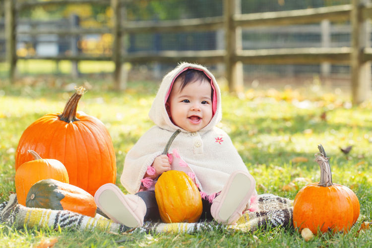 Cute baby girl wearing warm clothing sitting with pumpkins on land