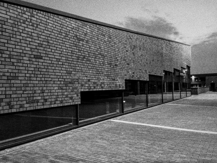 Empty alley along brick wall