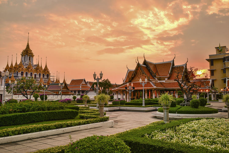 tropical swimming pool at night and Buddhist Temple in thailand Architecture Built Structure Building Exterior Building Sunset Sky Religion Belief Cloud - Sky Spirituality Place Of Worship Plant Nature No People Travel Destinations Orange Color City The Past Outdoors Spire