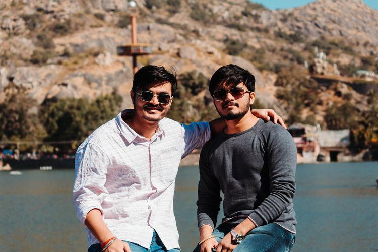 Portrait of friends wearing sunglasses against lake