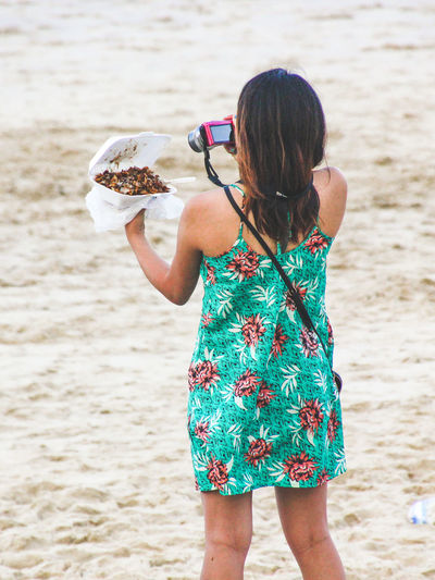 Rear View Of Woman Photographing Food At Beach