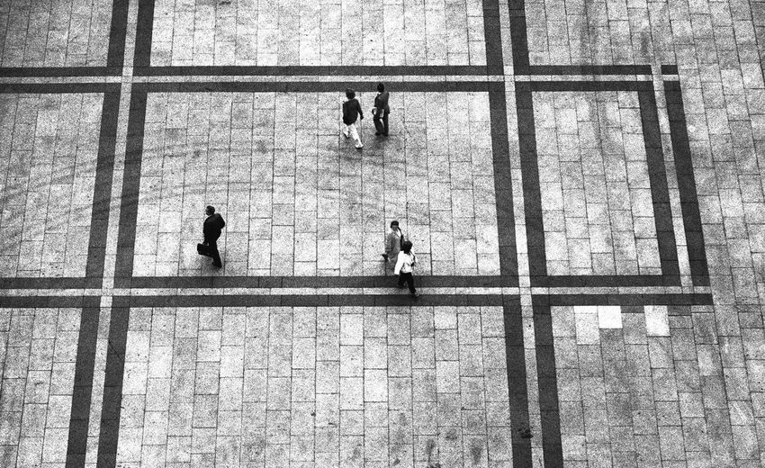 High Angle View Of People Walking On Tiled Floor