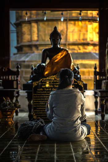 Rear view of woman sitting on floor against statue in temple