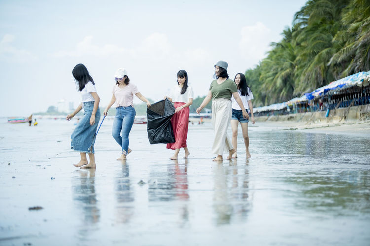 Female friends collecting garbage at beach